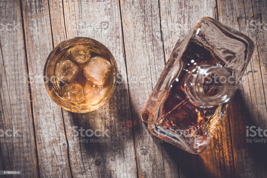 Overhead shot of whiskey bottle and whiskey glass with ice cubes on an old wooden table stock photo