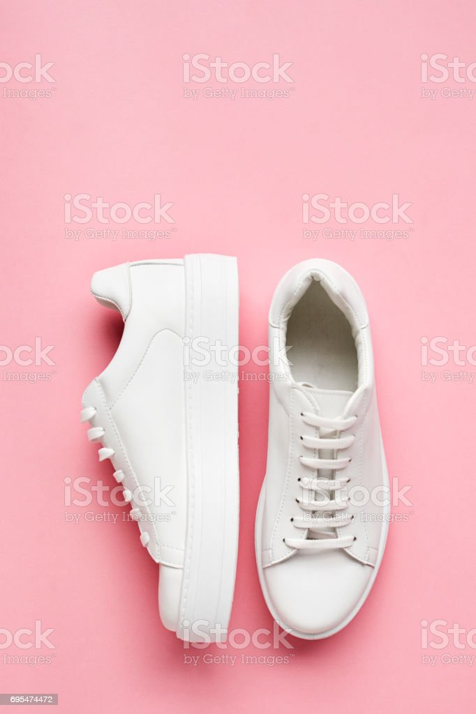 Tiro arriba de zapatillas blancas en fondo rosa foto de stock libre de derechos