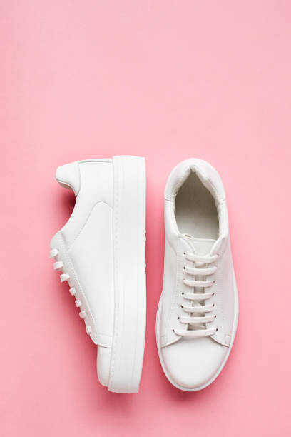 overhead shot of white sneakers on pink background - pair stock photos and pictures