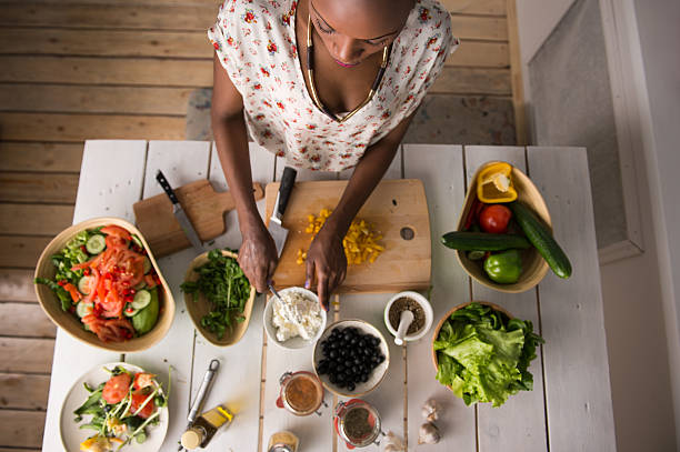 Overhead shot of woman preparing salad in a rustic kitchen stock photo