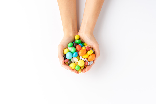 Overhead shot of woman's hands holding colourful sweets and candies isolated on white background
