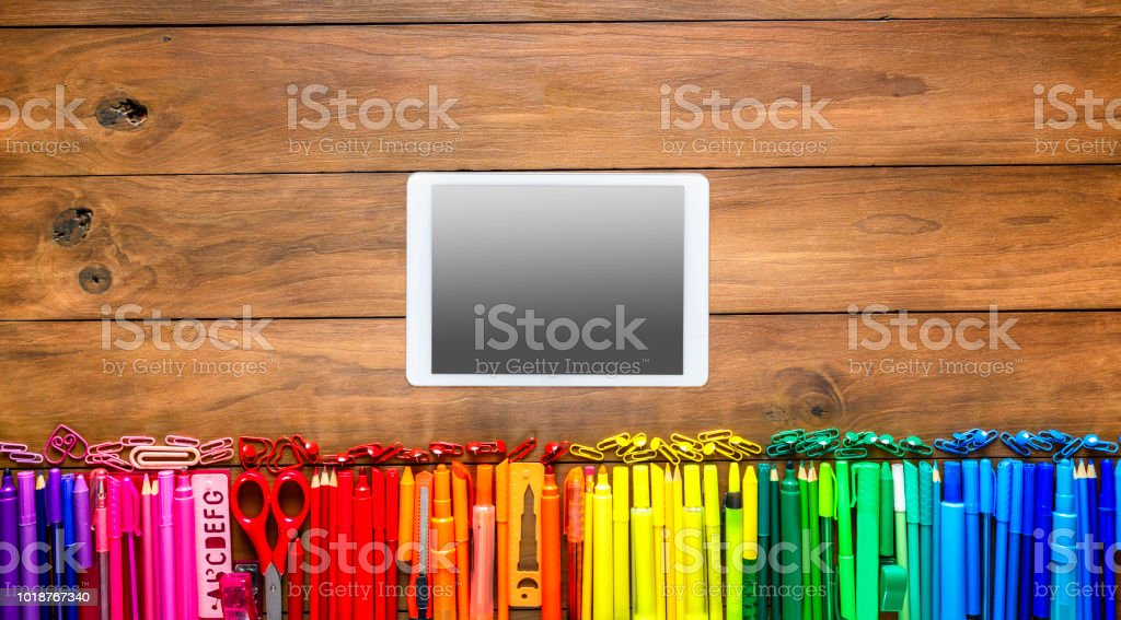 Overhead shot of wood table with assorted multi colored pencils and markers. Digital tablet into the frame. stock photo
