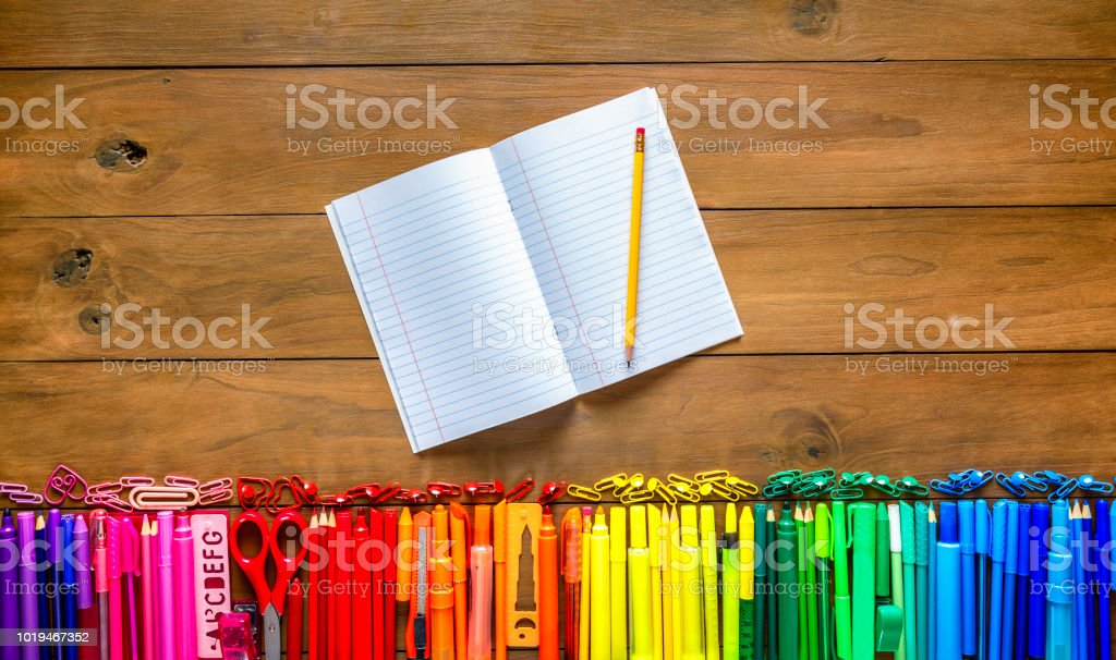 Overhead shot of wood table with assorted multi colored pencils and markers. Note book into the frame. stock photo