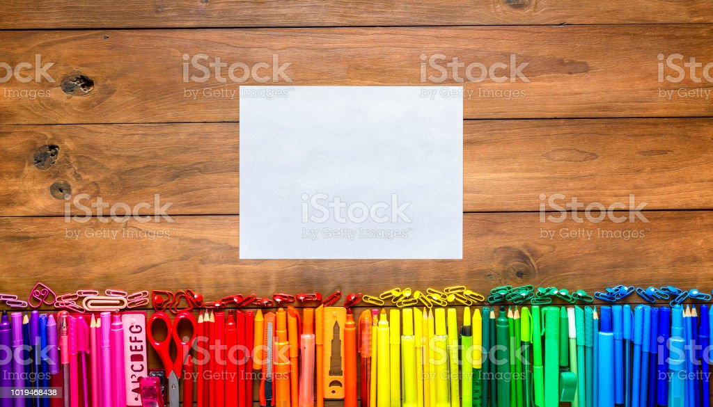 Overhead shot of wood table with assorted multi colored pencils and markers. Blank sheet of paper into the frame. stock photo