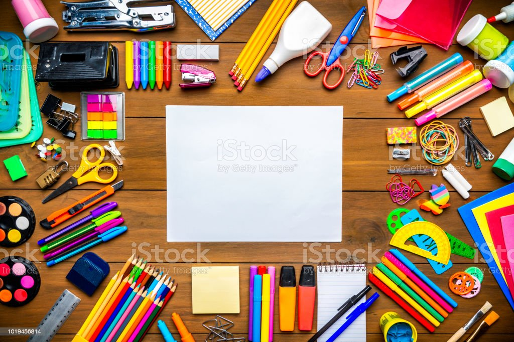 Overhead shot of wood table with blank paper and frame of school office supplies stock photo