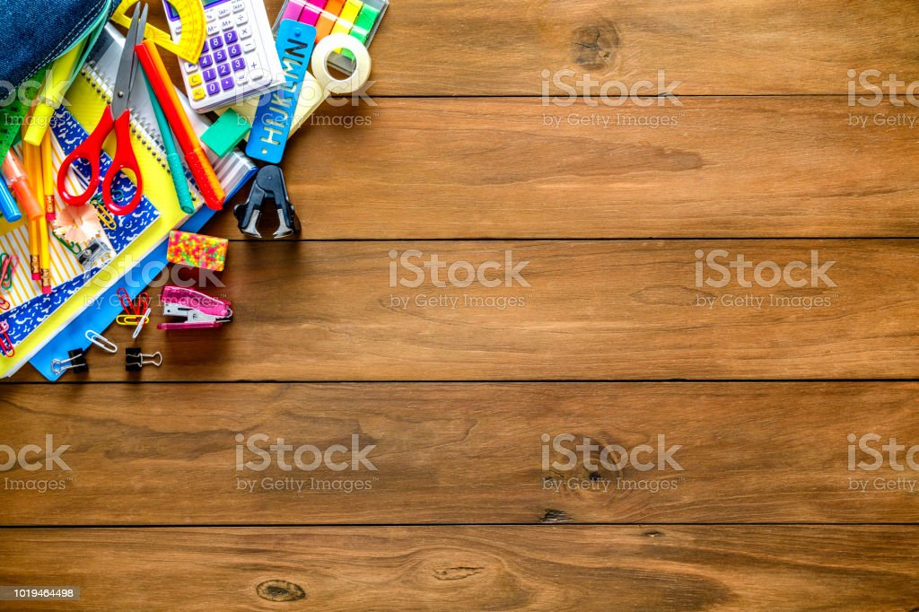 Overhead shot of wood table with frame of back to school office supplies stock photo