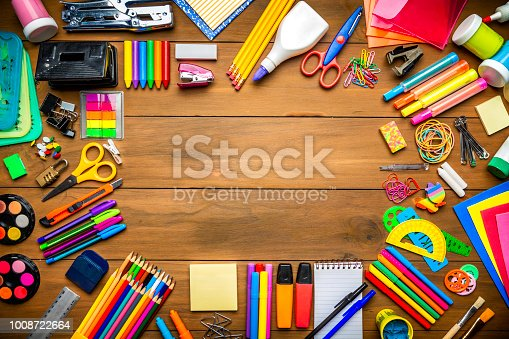 Back to school themes. Overhead shot of wood table with frame of school office supplies