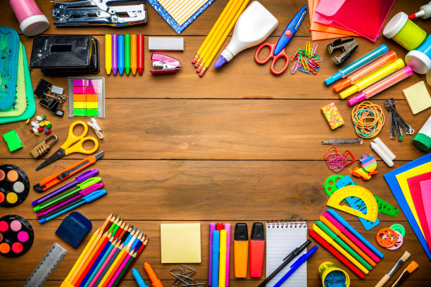 overhead shot of wood table with frame of school office supplies - school supplies stock pictures, royalty-free photos & images