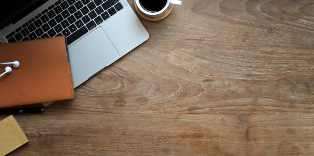 Overhead shot of wooden desk with laptop Overhead shot of wooden desk with laptop, supplies and copy space in modern working space high angle view stock pictures, royalty-free photos & images