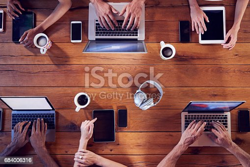 684006316istockphoto Overhead shot of young adults using technology at a table 684006316