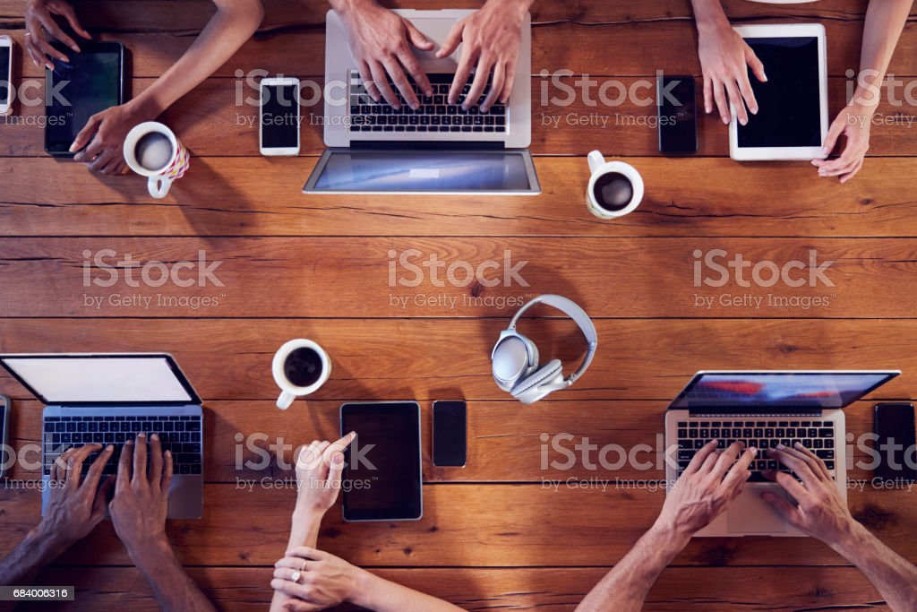 Overhead shot of young adults using technology at a table stock photo