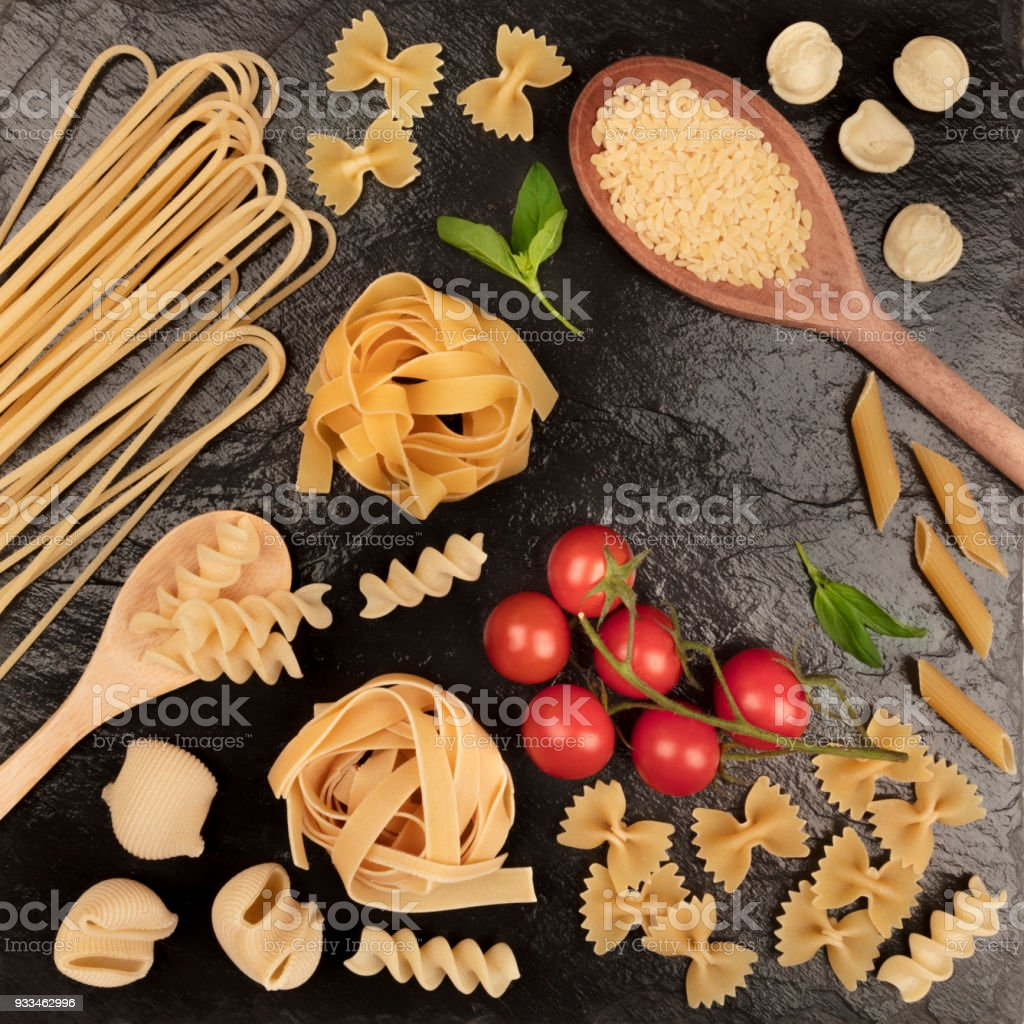 Overhead square photo of different types of pasta on black stock photo