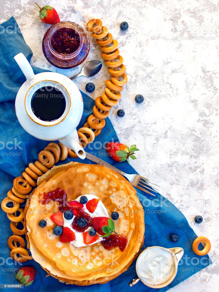 Overhead stack of thin pancakes poured with sour cream and decorated with fresh strawberries and blueberries. The concept of Russian tea party at holiday Maslenitsa, Shrovetide stock photo