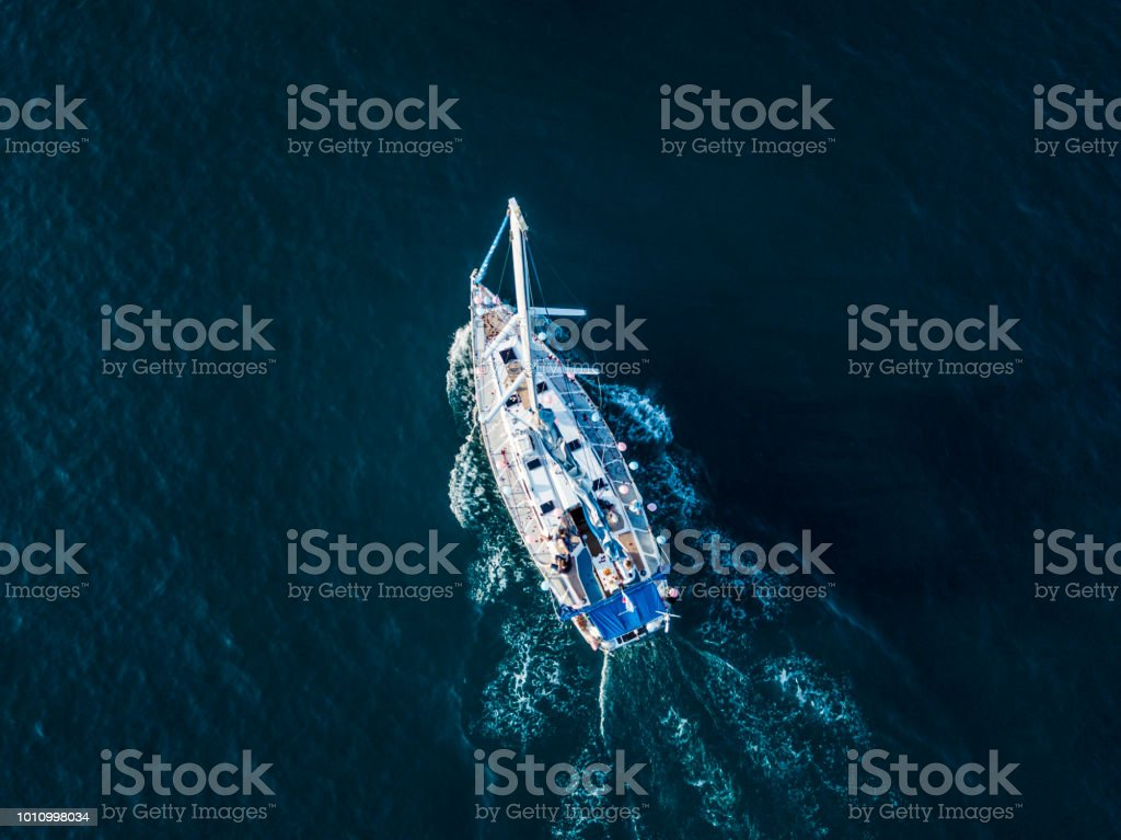 3ee7b9a7ca4f overhead top aerial view of luxury sail boat in the crystal clear blue sea  water lagoon