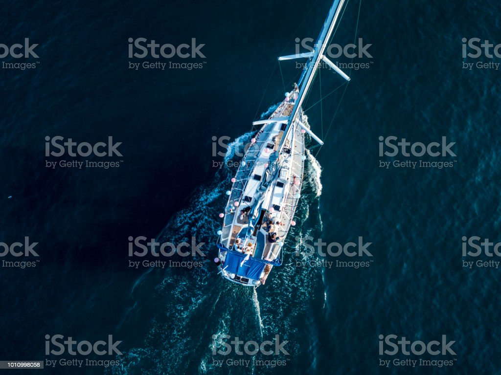 e92e26a3d8ef Overhead top aerial view of luxury sail boat in the crystal clear blue sea  water lagoon - Stock image .
