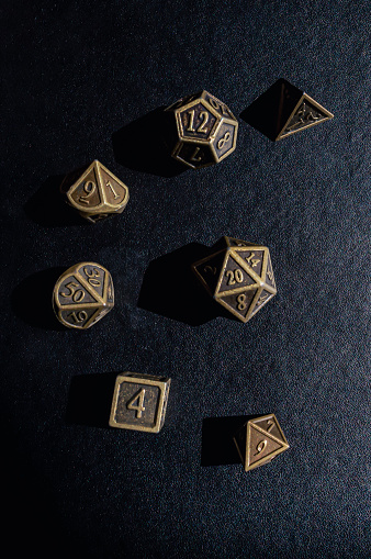 Overhead vertical image of a bronze colored set of Role-playing game dice