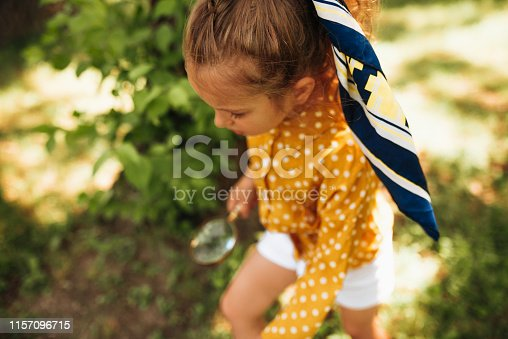 istock Overhead view image of little girl exploring the nature with magnifying glass outdoors. Child playing in the forest with magnifying glass. Curious kid searching with magnifier on the grass in the park 1157096715