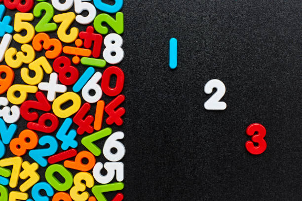 Overhead view of 123 toys by colorful numbers on blackboard stock photo