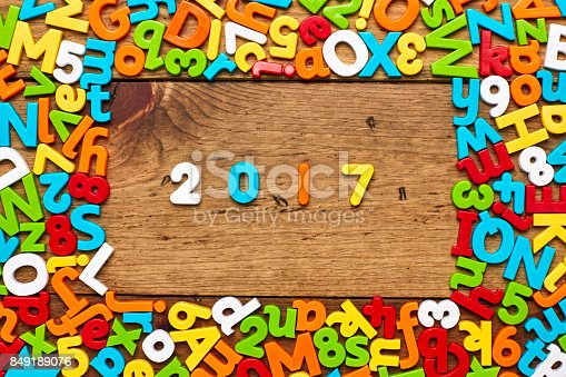 849191694 istock photo Overhead view of 2017 surrounded by colorful letters on wood 849189076