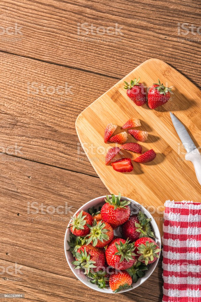 Overhead View Of A Bowl Of Strawberries With Towel A Knife