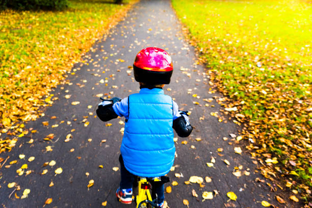 Overhead view of a boy riding bike with safety helmet outdoors at autumn park stock photo