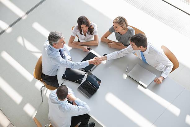 sopra vista di un gruppo di business in una riunione che agitano le mani - business meeting, table view from above foto e immagini stock