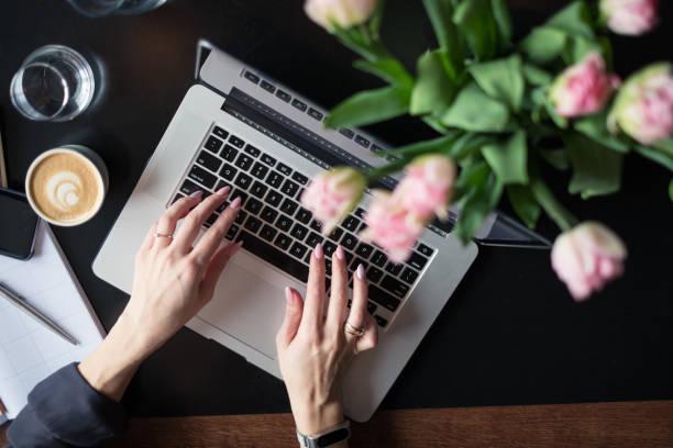 visão aérea de um blogger feminino escrevendo no laptop - mulher flores - fotografias e filmes do acervo