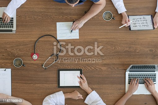 Ariel view of a medical meeting taking place around a conference table with various medical practitioners and professionals