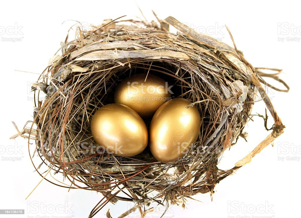 Overhead view of a nest with three golden eggs stock photo
