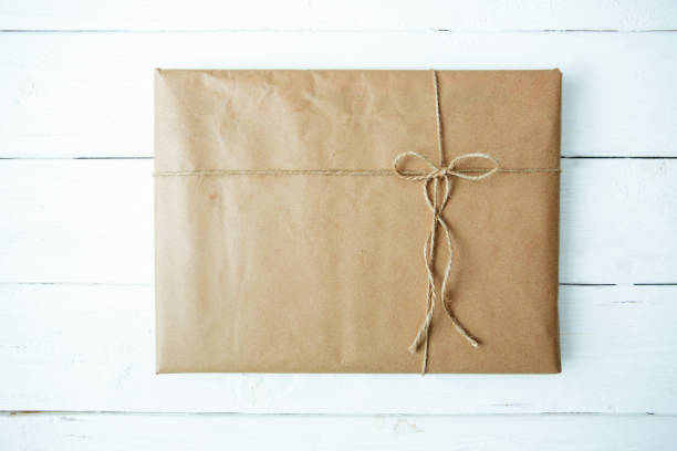 Overhead view of a single holiday package wrapped with eco friendly craft paper and tied with twine. Square format on a rustic wooden table. stock photo