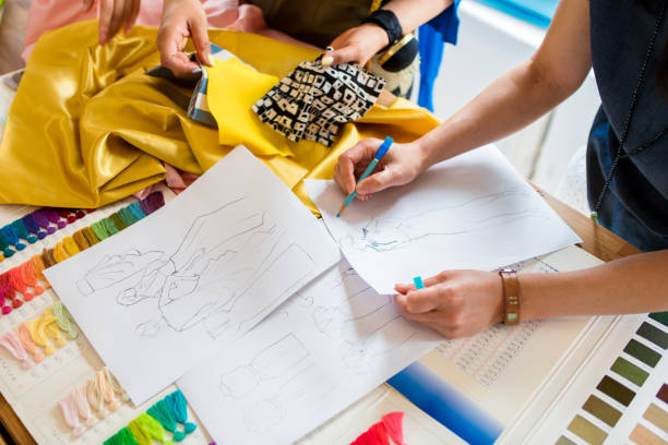 Overhead view of a team of fashion designers working Over the shoulder view of a team of clothing designers working on a new pattern. Kyoto, Japan. May 2016 fashion designer stock pictures, royalty-free photos & images