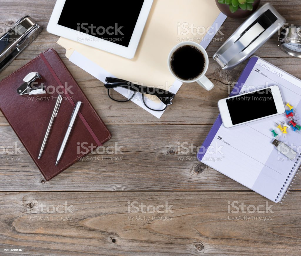 Overhead view of a working desktop on rustic wood setting royalty-free stock photo