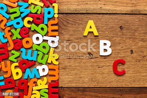 849181972istockphoto Overhead view of ABC by colorful alphabets on wooden background 849181156