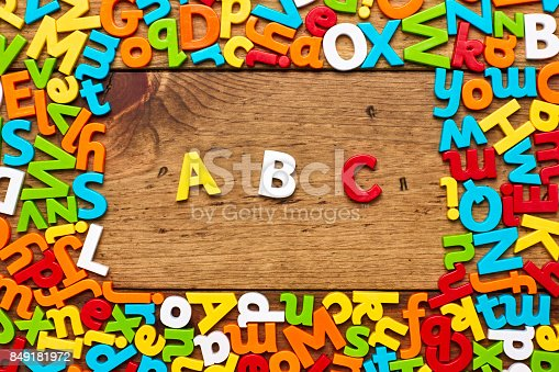 849191694 istock photo Overhead view of ABC surrounded with colorful alphabets on wood 849181972