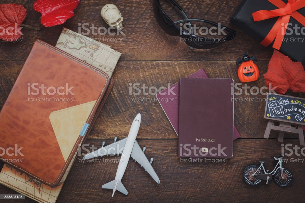 Overhead view of accessory Happy Halloween with items to travel background concept.Mix several object on the modern rustic brown wooden at home office desk.Equipment for traveler or teenage and adult. stock photo