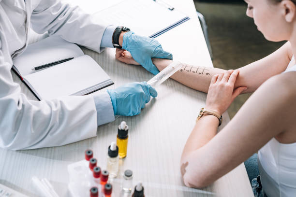 overhead view of allergist holding ruler near marked hand of woman overhead view of allergist holding ruler near marked hand of woman immunology stock pictures, royalty-free photos & images