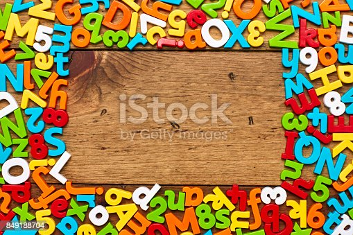 849191694 istock photo Overhead view of alphabets and numbers in frame on wood 849188704