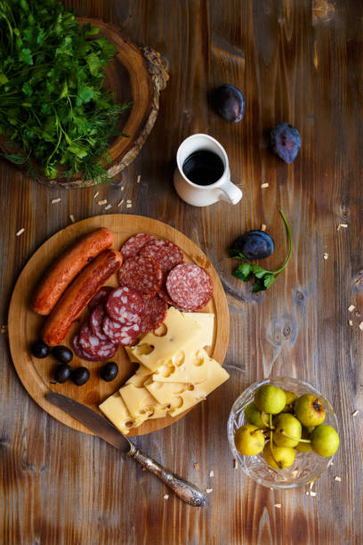 Overhead view of aperitif table Meat snack, fried sausages, cheese, salami, olives and a glass of wine on a dark table Menu and restaurant concept stock photo