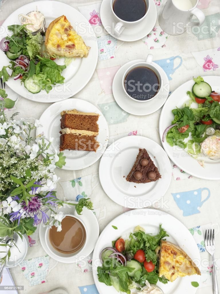 Overhead view of bacon and onion quiche, salad, cakes and coffee royalty-free stock photo