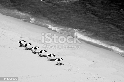 Overhead view of beach chairs and surf of the Atlantic Ocean in West Palm Beach, Florida captured in black and white
