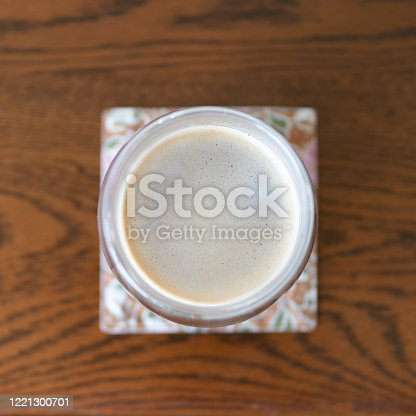 Overhead view of cup of black coffee on dining table in morning sun with selective focus
