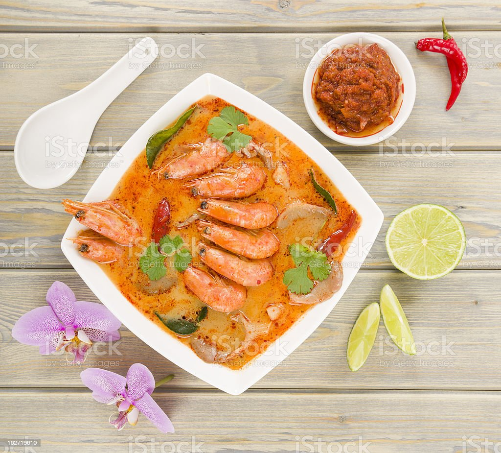 Overhead view of bowl of Tom Yum Nam Khon on a wooden table stock photo