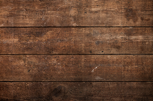 A wood background with multiple planks placed close together.  The planks feature a variety of light and dark brown shades.