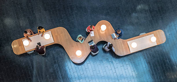 Overhead view of business meetings Panoramic overhead view of several business meetings going on in the communal area of a modern office building. directly above stock pictures, royalty-free photos & images