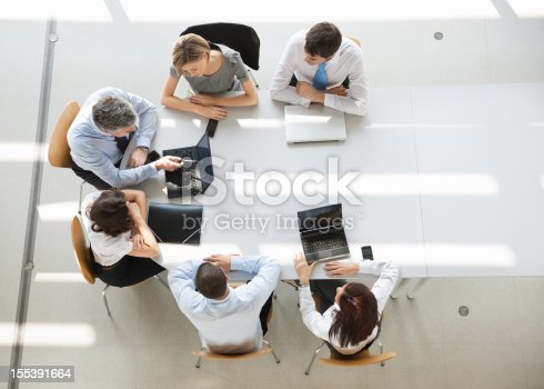 Business People In Meeting. A group of six men and women (three man and three woman) sitting around an oval white table having a business meeting. They all are dressed in business causal, and have their laptops out, only two are being used. They are sitting in simple wooden chairs.