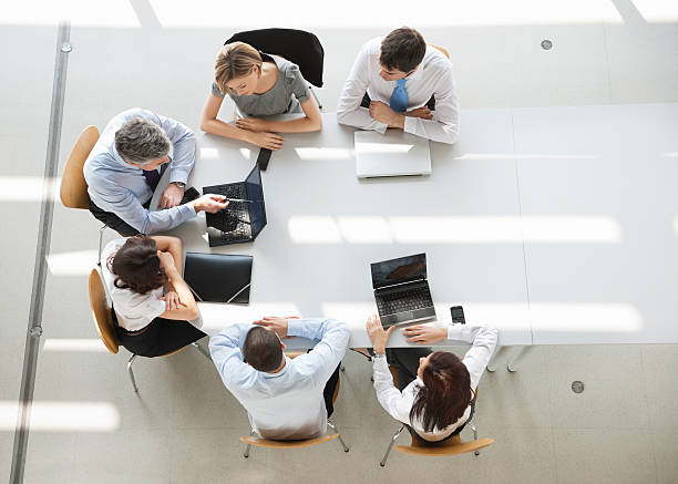 Overhead view of business people in a meeting Business People In Meeting. A group of six men and women (three man and three woman) sitting around an oval white table having a business meeting. They all are dressed in business causal, and have their laptops out, only two are being used. They are sitting in simple wooden chairs.  directly above stock pictures, royalty-free photos & images