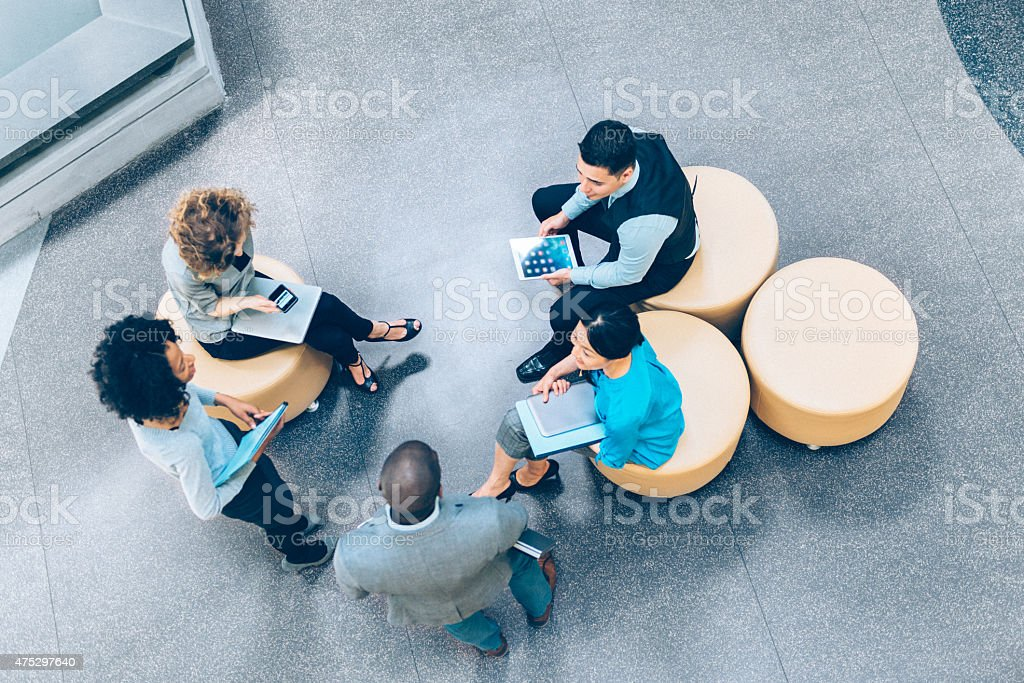 Overhead view of business people in a meeting Overhead view of multiracial business team having a meeting in the Office Lobby 2015 Stock Photo
