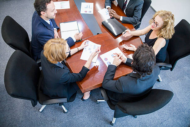 Overhead view of business team meeting in conference room Overhead view of business team meeting in conference room governing board stock pictures, royalty-free photos & images