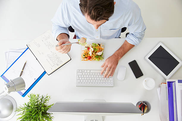 overhead view of businessman working at computer in office - eating technology stock pictures, royalty-free photos & images