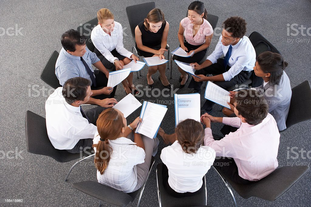 Overhead View Of Businesspeople Seated In Circle At Company Semi stock photo